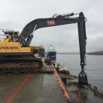 Digger removing dredge from harbour