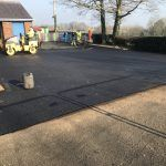 ATG employees rolling new tarmac over playground