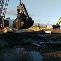 Crane depositing dredge into lined area