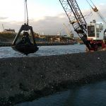 Crane attachment lifting dredge from river