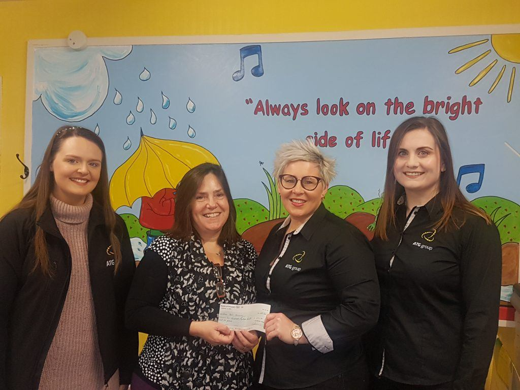 ATG staff giving a cheque to the manager of Home-Start Causeway
